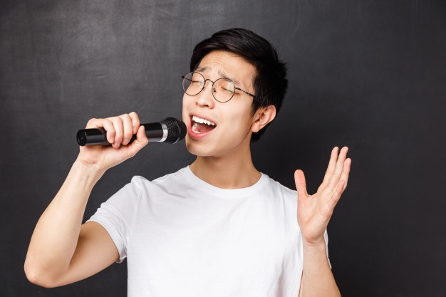 leisure-people-music-concept-close-up-portrait-passionate-carefree-asian-guy-likes-singing-songs-holding-microphone-raising-one-hand-perform-fron-friends-karaoke-party_1258-10026