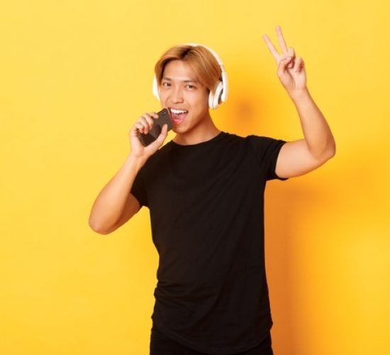 sassy-handsome-asian-guy-headphones-playing-karaoke-app-singing-into-mobile-phone-microphone-showing-peace-gesture-standing-yellow-wall_1258-17479